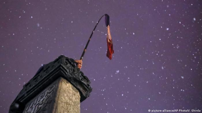 A Romanian flag held by a protester is seen against the night sky