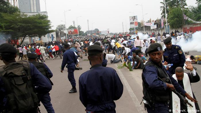 Anti-Kabila protesters scatter as police fire tear gas to break-up the crowd.