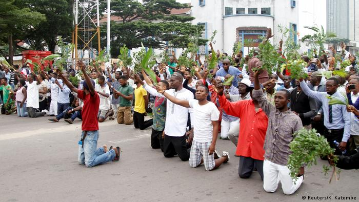 Protestors against President Kabila kneeling and chanting slongans on the streets of Kinshasa (Reuters/K. Katombe)
