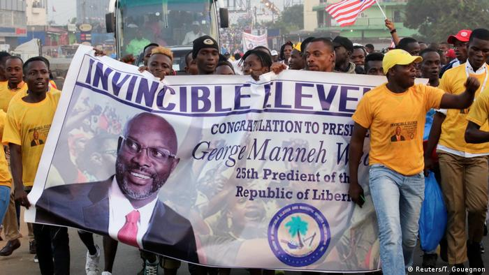 Supporters of the new president carrying a banner with his face eith the word invincible on it