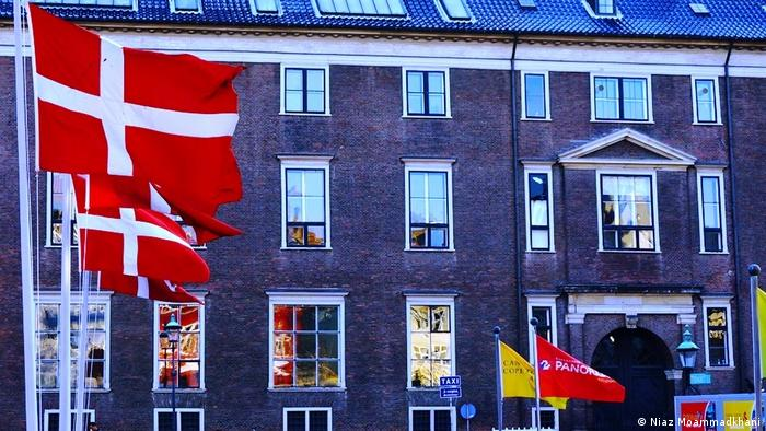 Denmark, Copenhagen, brick building with Danish flags (Niaz Moammadkhani)
