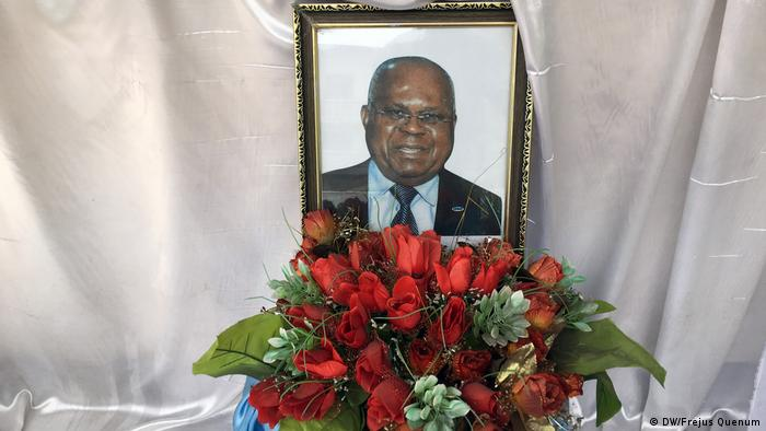 A picture of the late DR opposition leader Etienne Tshisekedi behind a bunch of red flowers, leaning against the white sheet of his coffin