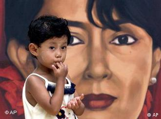A girl stands in front of a poster of Aung San Suu Kyi