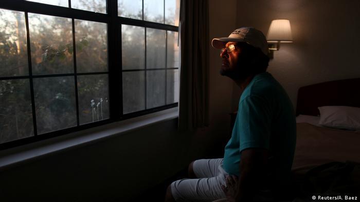 Hombre mirando por una ventana.