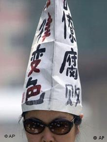 A Chinese petitioner wears a hat with the words Officials Corrupt, Changed Judiciary in Beijing, China, Monday, May 4 , 2009. Protesters timing their protest on the 90th anniversary of May Fourth protest movement strung banners from a Beijing hotel and flung handbills off the roof seeking redress for a litany of grievances and in hopes of winning attention from authorities to their plight. (AP Photo/Ng Han Guan)