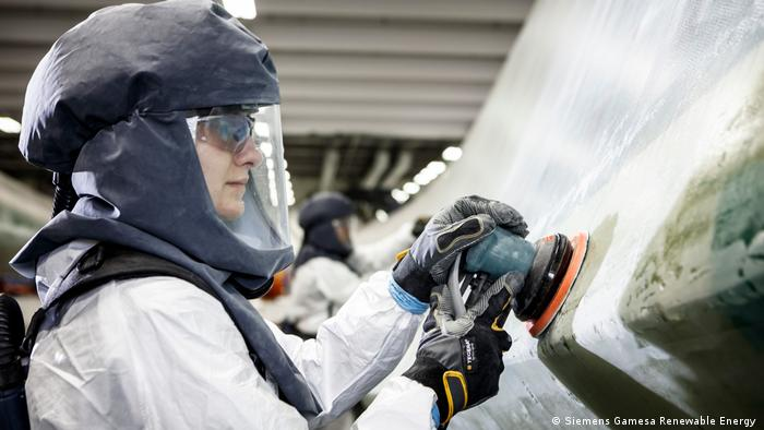 Photo: A worker smooths a rotor blade at the factory. (Source: Siemens Gamesa Renewable Energy )