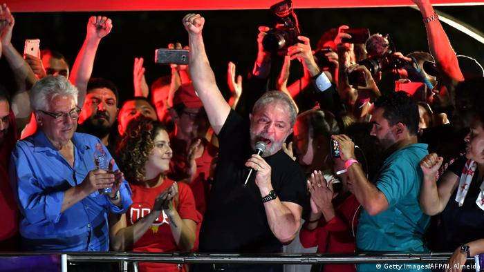 Lula Da Silva raises his fist at a protest with supporters