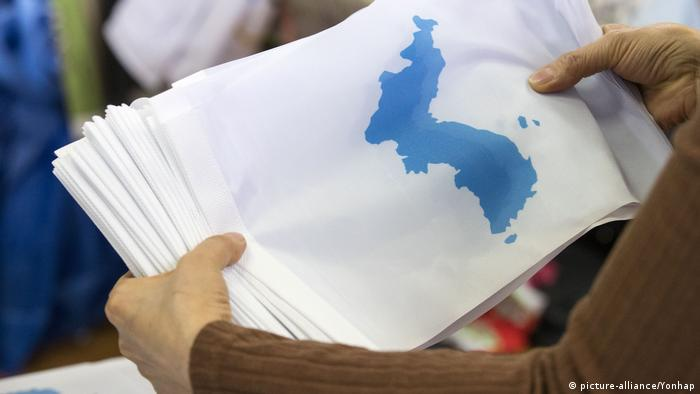 A worker takes a look at Korean Unification flags (picture-alliance/Yonhap)