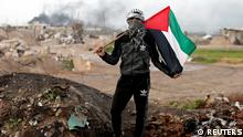 A protester holds a Palestinian flag as he poses for a photograph at the scene of clashes with Israeli troops near the border with Israel, east of Gaza City, January 19, 2018. The battle between us and the Israeli occupation has been ongoing for decades. We will continue to protest and resist as long as there is one Israeli occupier on our land. Trump and anyone else in this world will not be able to control our anger, he said. REUTERS/Mohammed Salem SEARCH PROTESTER PALESTINIAN FOR THIS STORY. SEARCH WIDER IMAGE FOR ALL STORIES.