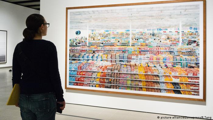 A woman looks at Andreas Gursky's 99 Cent photo, which shows rows of products in a supermarket (picture-alliance/Zumapress/R.Tang)