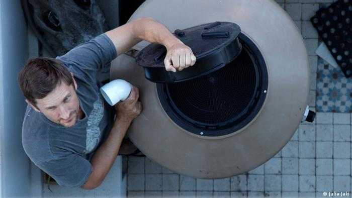 A man holding a drain pipe is installing a water tank.
