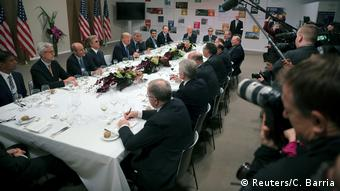 The US president and his dinner guests sit around the table at Davos as press look on (Reuters/C. Barria)
