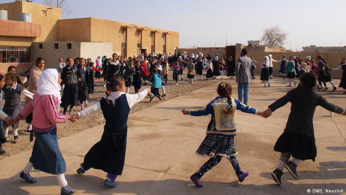 Pupils dancing outside their school in Hawija