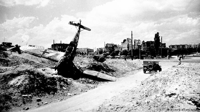 A view of a bombed-out landscape, with ruined buildings in the distance.