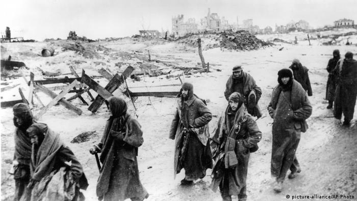 A group of raged-looking men walking past a destroyed landscape.