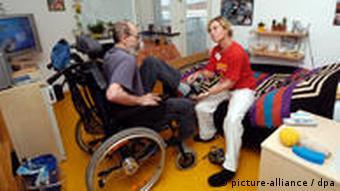 Женщина помогает инвалиду