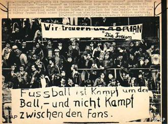 Fans hold a banner that says football is a fight for the ball, not a fight between fans