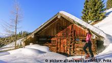 Junge Frau bei einer Skiwanderung vor Almhütte am Bischling oberhalb von Werfenweng, Pongau, Salzburger Land (picture-alliance/picturedesk/F. Pritz)