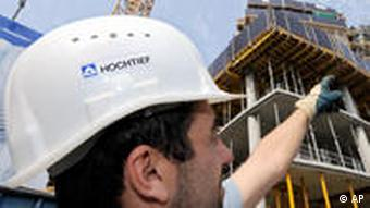 A man wearing a Hochtief hardhat in front of a building site