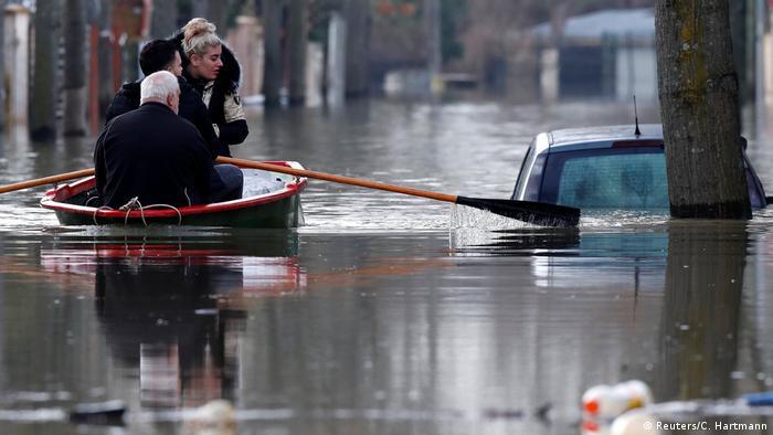 Drei Personen in einem Ruderboot, daneben ein Auto halb im Wasser (Foto:Reuters)