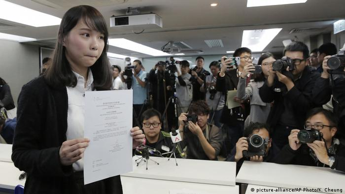 Agnes Chow presents the government document barring her from participating in elections