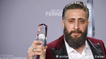 Schauspieler Kida Khodr Ramadan mit Bart und bordeauxfarbenen Sakko hält den Deutschen Fernsehpreis in der Hand (Foto: picture-alliance/dpa/H. Kaiser).