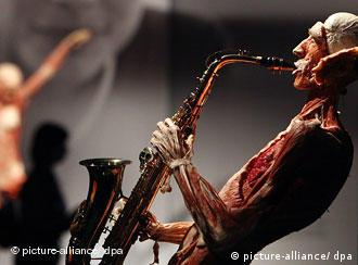 A plastinated corpse of a woman is posed as though she is playing a saxophone in an April 2009 Body Worlds exhibit