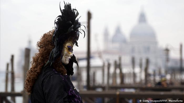 A masked reveller dressed in a period costume takes part in the Venice Carnival