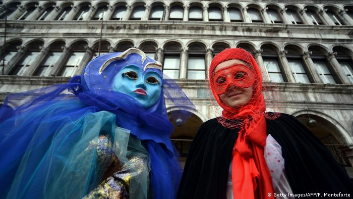 Masked revellers dressed period costumes take part in the Venice Carnival