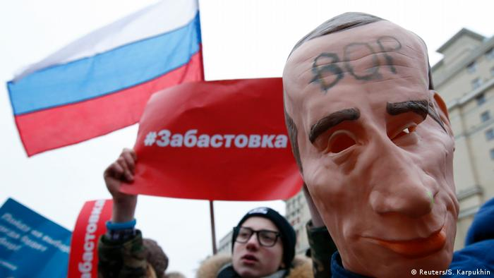 A large rubber head of Vladimir Putin is carried along in the protest.