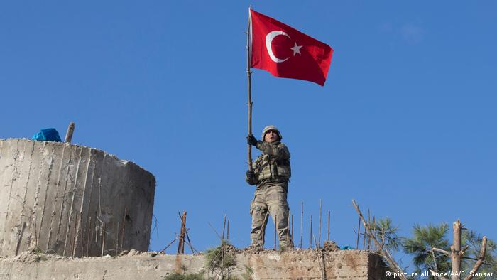 Soldier holding Turkish flag at Mount Baraja in Syria