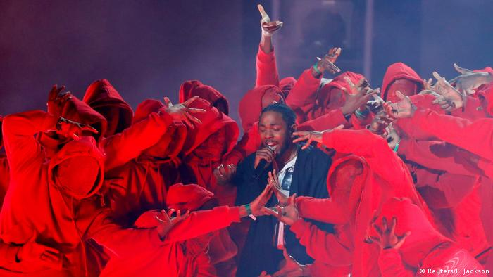Kendrick Lamar performing at the Grammys surrounded by a tumult of red-costumed dancers