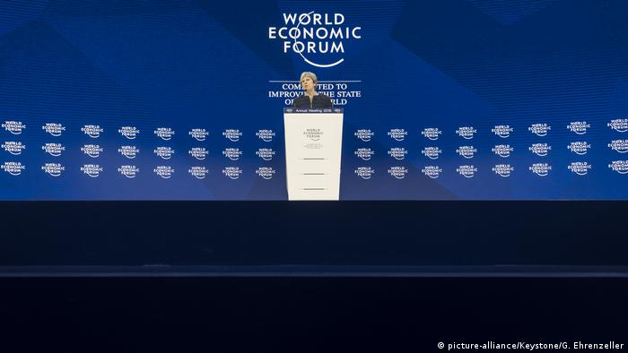 Theresa May stands at a podium at the World Economic Forum