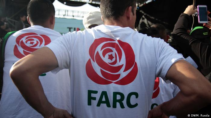 A campaign operative displays the FARC political movement's logo on a t-shirt