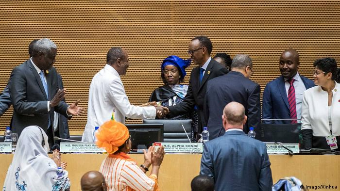 Alpha Conde and Kagame shake hands surrounded by other AU functionaries (Imago/Xinhua)