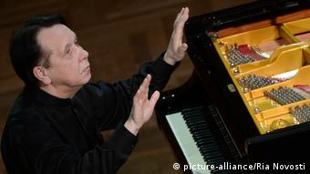 Mikhail Pletnev sits at the piano, waving his hands as though conducting