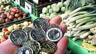 A hand filled with euros is seen in front ot a vegetable stand