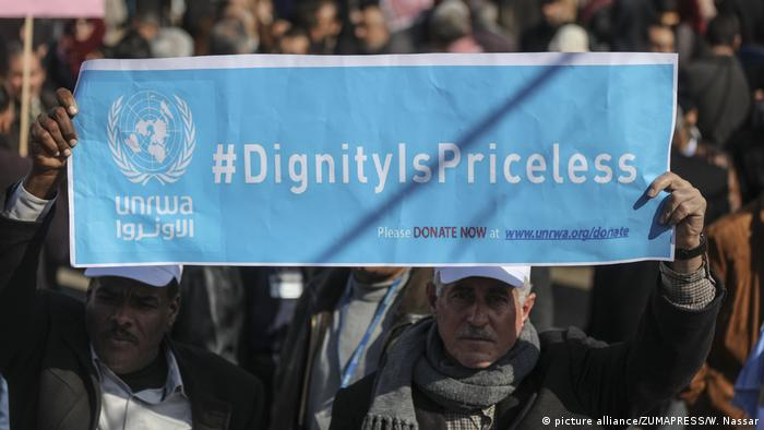 Palestinian UNRWA employees hold up signs as they protest the US decision to reduce its funding on January 29, 2018 in Gaza