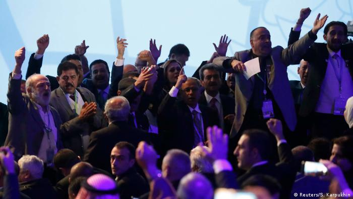 Participants raise slogans during the opening session of the Syrian peace conference