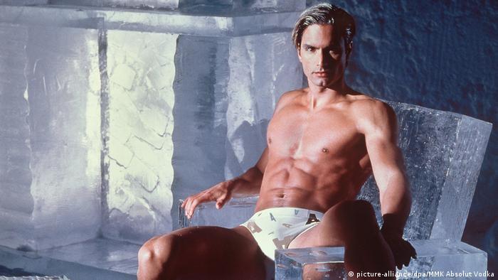 Model Marcus Schenkenberg posiert nur in Shorts bekleidet auf einem Eissessel.
