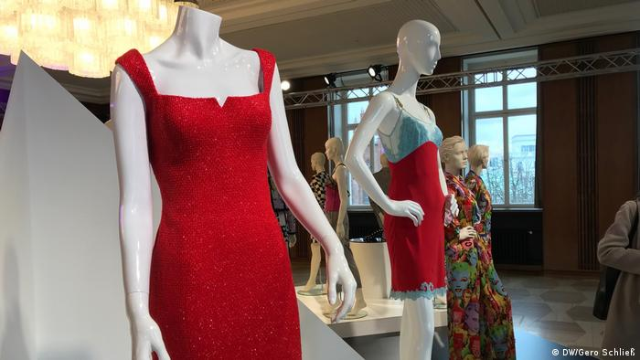 Rotes Trägerkleid an einer Puppe im Ausstellungsraum.