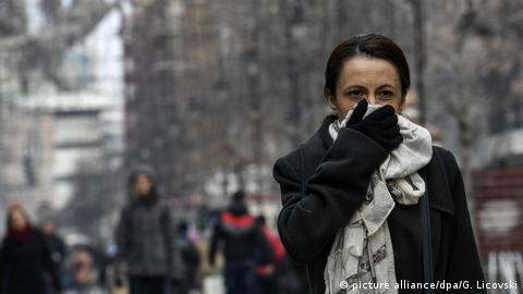 A woman is holding a scarf in front of her face to protect herself from exhaust fumes (photo: picture alliance/dpa/G. Licovski)