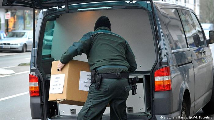 A German customs agent carries away a box of evidence seized during an illegal work raid (picture-alliance/dpa/H. Battefeld)