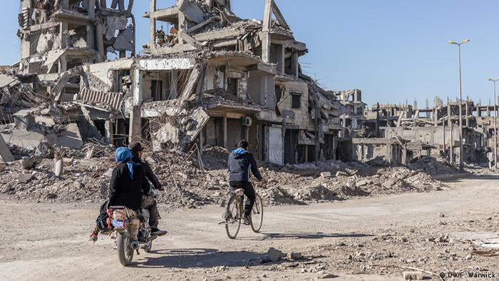 Syrians cycling past destroyed buildings