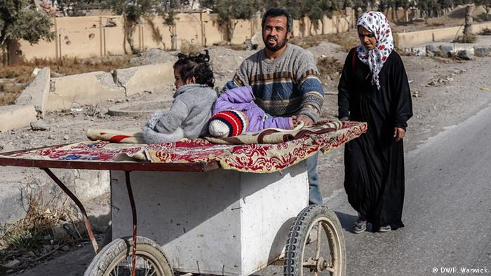 A man in Raqqa pushing a home-made wheelie box
