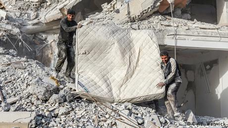 Two men carrying a mattress through the rubble