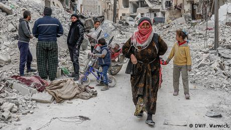 A group of people standing next to a destroyed building