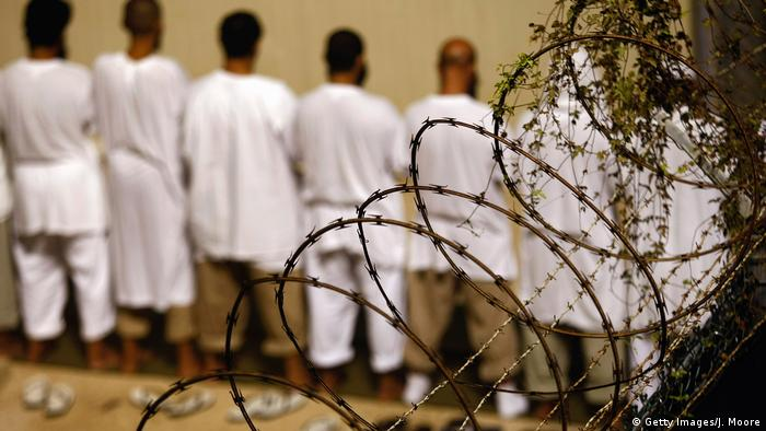 Detainees stand during an early morning Islamic prayer at the US military prison for enemy combatants on October 28, 2009 in Guantanamo Bay, Cuba.