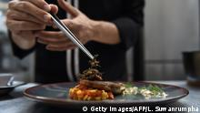 This photo taken on August 15, 2017 shows edible winged ants being placed on a fish fillet inside the kitchen of Insects in the Backyard, which says it offers the first insect-based fine-dining menu, in Bangkok. Bugs are creeping onto the menu of some of Bangkok's high-end restaurants as the capital's gourmands leap on the latest global food trend with a sustainable agenda. / AFP PHOTO / Lillian SUWANRUMPHA / TO GO WITH Thailand-food-insects-lifestyle, FEATURE by Sippichai KUNNUWONG and Delphine THOUVENOT (Photo credit should read LILLIAN SUWANRUMPHA/AFP/Getty Images)