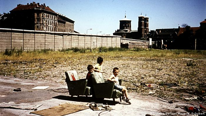 Children sit on chairs in a open abandoned area in front of the Berlin Wall (Stiftung Berliner Mauer/W. Schubert)